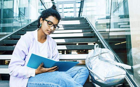 Student sitting on stairs with a note book wearing glasses